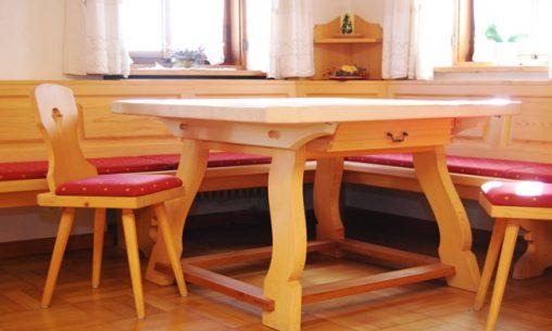 Individuell eingerichtetes Wohnzimmer mit Sideboard und Vitrine aus Naturholz und gemütlichem Ecksofa