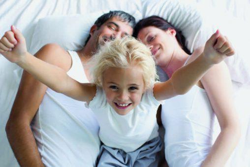 Mädchen mit Ihren Eltern im Bett